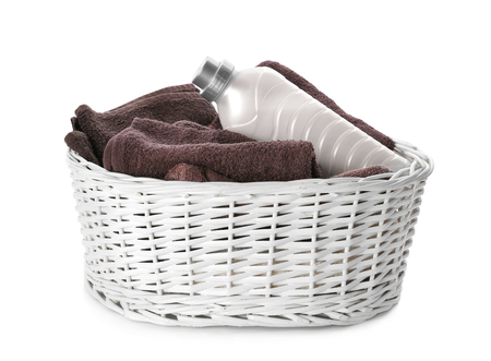 Basket with towels and laundry detergent on white background Standard-Bild
