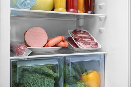 Meat products and vegetables in refrigerator, closeup