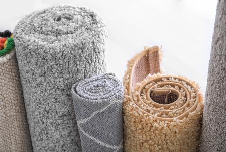 Gerollte bunte Teppiche auf weißem Hintergrund