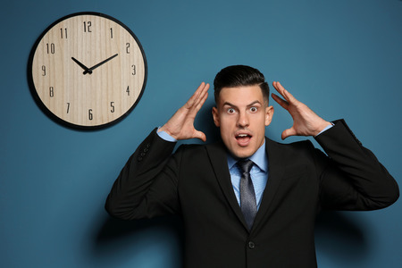 Shocked manager near wall with clock Imagens