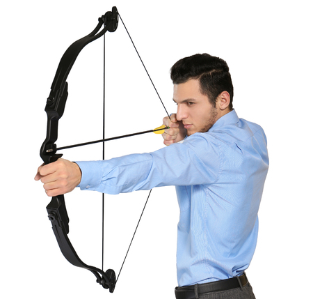 Young businessman practicing archery on white background