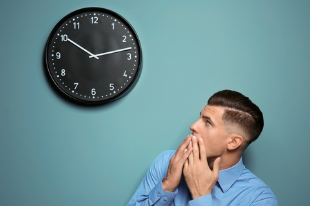 Shocked manager looking at clock hanging on wall