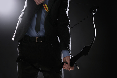 Businessman practicing archery on dark background