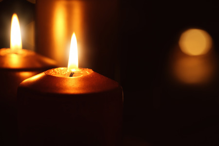 Beautiful burning candles in darkness, closeup