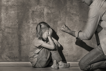 Man threatening his daughter indoors, black and white effect Imagens