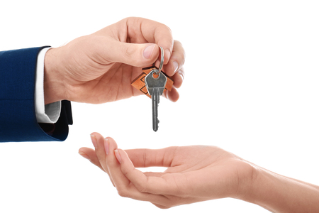 Real estate agent giving key of new house to woman on white background