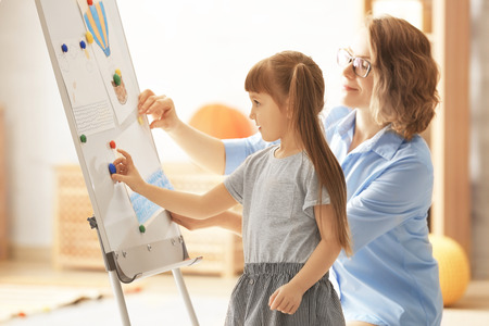 Female psychologist with cute little girl during art therapy