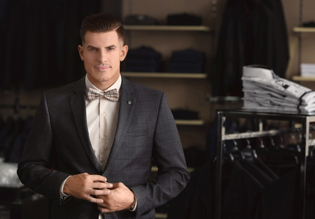 Handsome young man wearing suit in shop