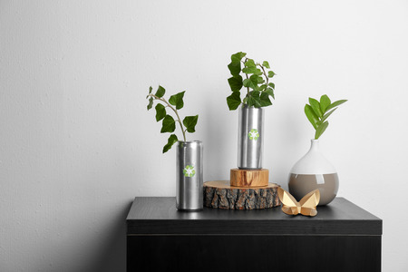 Tin cans with plants on table near light wall. Waste recycling concept Stock Photo