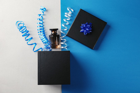 Opened gift box, perfume and streamers on color background, top view