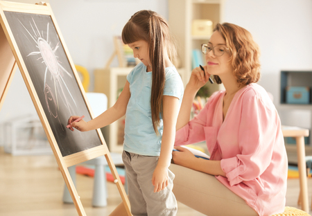 Cute little girl with female psychologist during art therapy