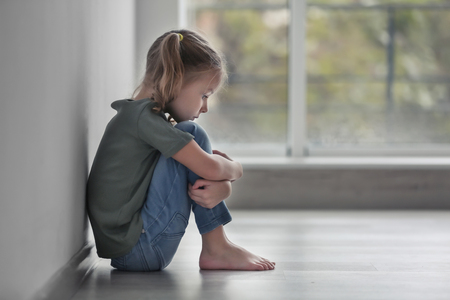 Sad little girl sitting on floor indoors 版權商用圖片 - 112549028