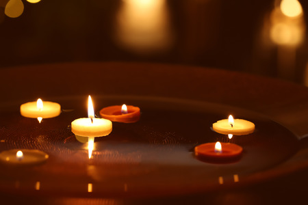 Small burning candles floating in plate with water