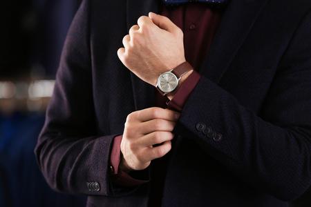 Junger Mann im eleganten Anzug auf unscharfem Hintergrund