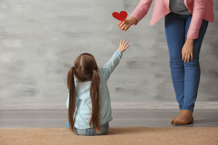 Woman giving heart to sad little girl indoors. Psychological support Foto de archivo - 112549285