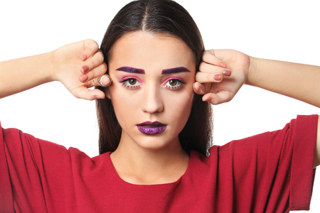 Young woman with dyed eyebrows and creative makeup on white background Stock fotó