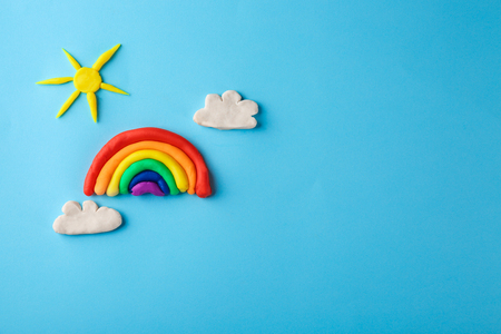 Plasticine rainbow, sun and clouds on color background Stock Photo