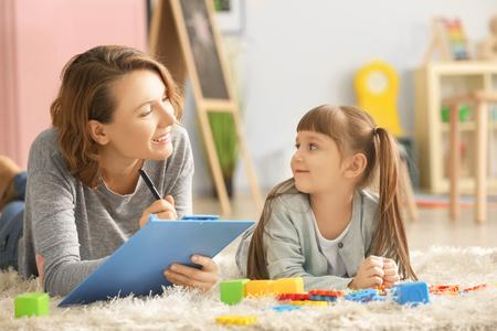 Psicóloga con niña linda durante la terapia de juego Foto de archivo
