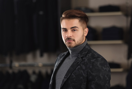 Young man in stylish clothes at menswear store