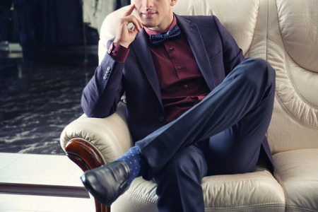 Young man in elegant suit sitting on sofa at menswear store