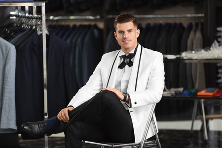 Handsome young man wearing elegant suit in shop