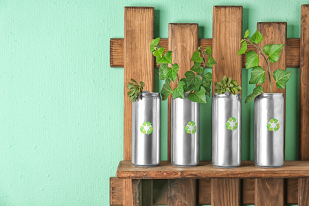 Tin cans with plants on wooden shelf near color wall. Waste recycling concept