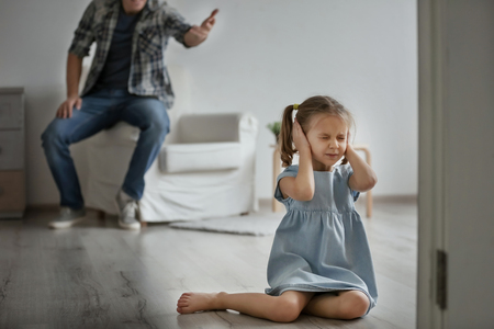 Man scolding his daughter at home