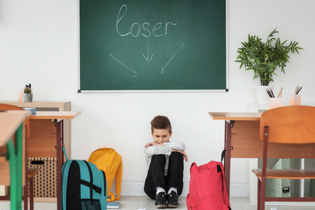 Little boy sitting under chalkboard with word