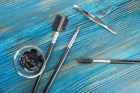 Set of tools for eyebrow dyeing and correction on wooden background