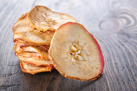 Tasty apple chips on wooden background Stock Photo