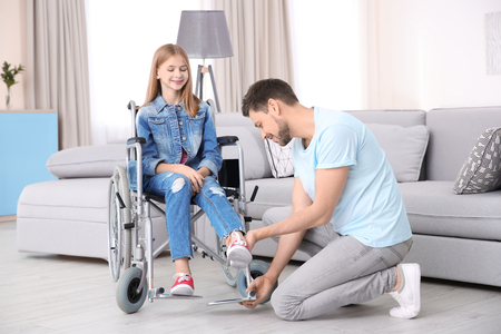 Young man taking care of teenage girl in wheelchair indoors