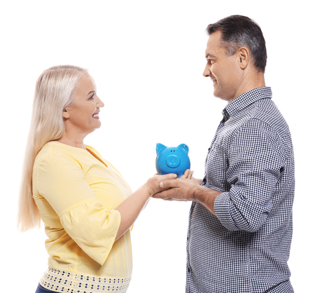 Mature couple with piggy bank on white background