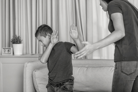 Woman scolding her son at home, black and white effect