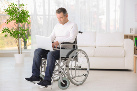 Mature man in wheelchair using laptop indoors 版權商用圖片