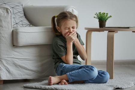 Trauriges kleines Mädchen, das drinnen auf dem Boden sitzt