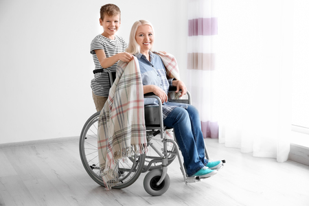 Little boy taking care of mature woman in wheelchair indoors