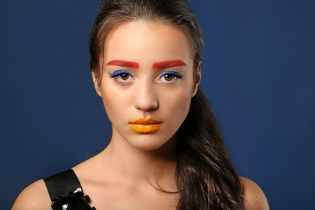 Young woman with dyed eyebrows and creative makeup on dark background Stock Photo