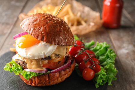 Tasty burger with fried egg on slate plate