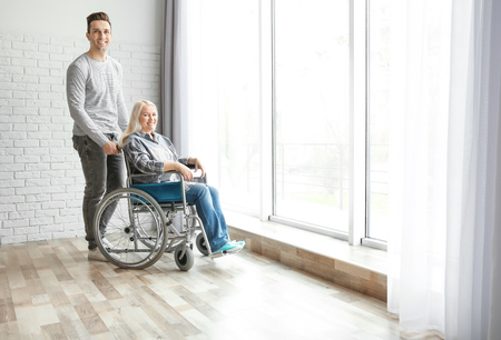 Young man taking care of mature woman in wheelchair indoors Imagens