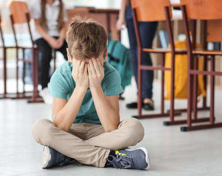 Little boy crying on floor in classroom. Bullying in school Stockfoto