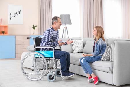 Mature man in wheelchair talking to teenage girl indoors Imagens