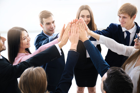 People putting hands together indoors. Unity concept Stock Photo