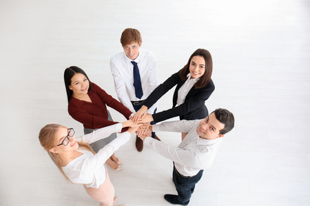 People putting hands together indoors. Unity concept Imagens