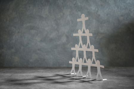 Pyramid made of paper people on grey background. Unity concept