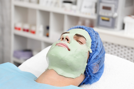 Young man with face mask in beauty salon