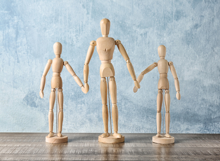 Wooden people holding hands together on table. Unity concept Standard-Bild