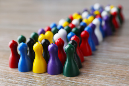 Group of color pawns on wooden table. Unity concept