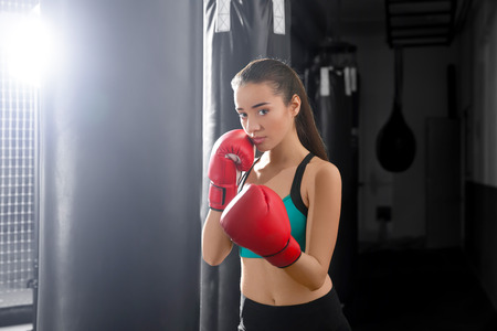 Portrait of young female boxer in gym
