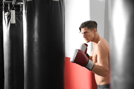 Male boxer training with punching bag in gym