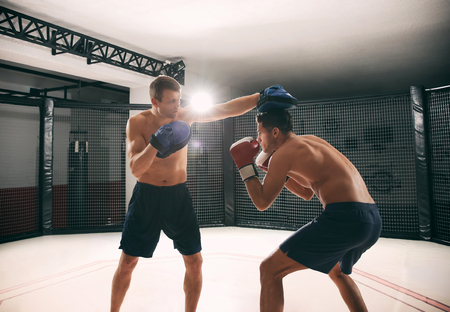 Young boxer training in gym with personal coach